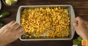 Mixing corn kernels with seasoning in a dish