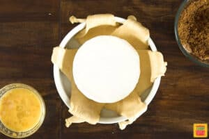 Baked brie in the centenr of crescent rolls in a white dish