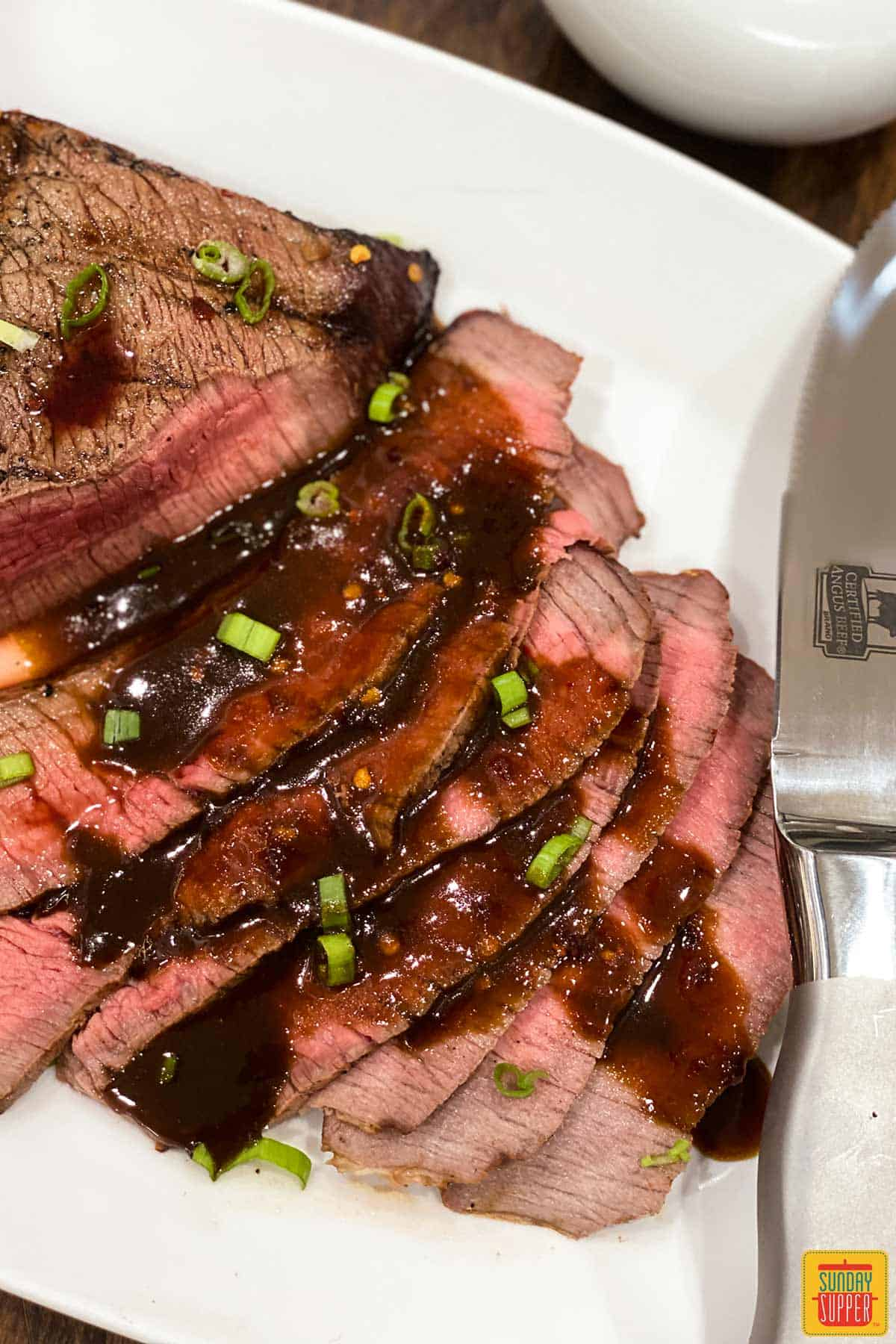 Slices of London broil on a plate with sauce