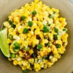 Mexican corn casserole on a plate with a lime wedge