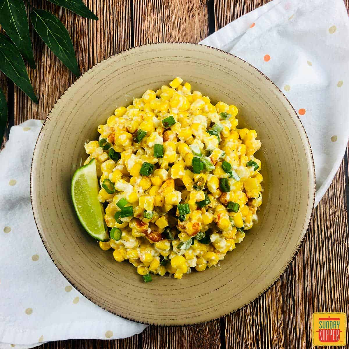 Mexican street corn casserole in a dish with a lime wedge
