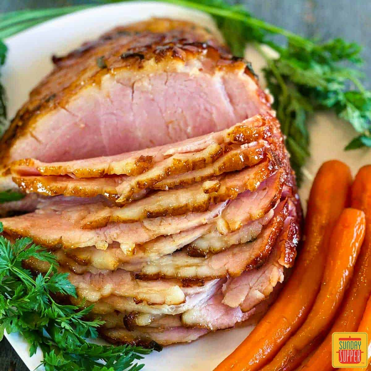 Air fryer ham with a side of greens and carrots on a white plate