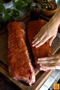 Patting dry rub onto ribs