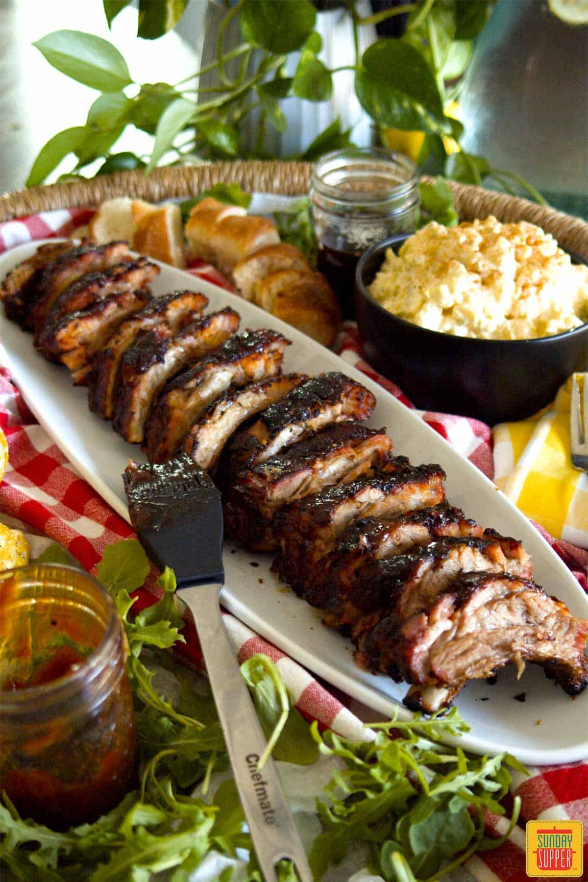 Baby back ribs on a white platter surrounded by side dishes