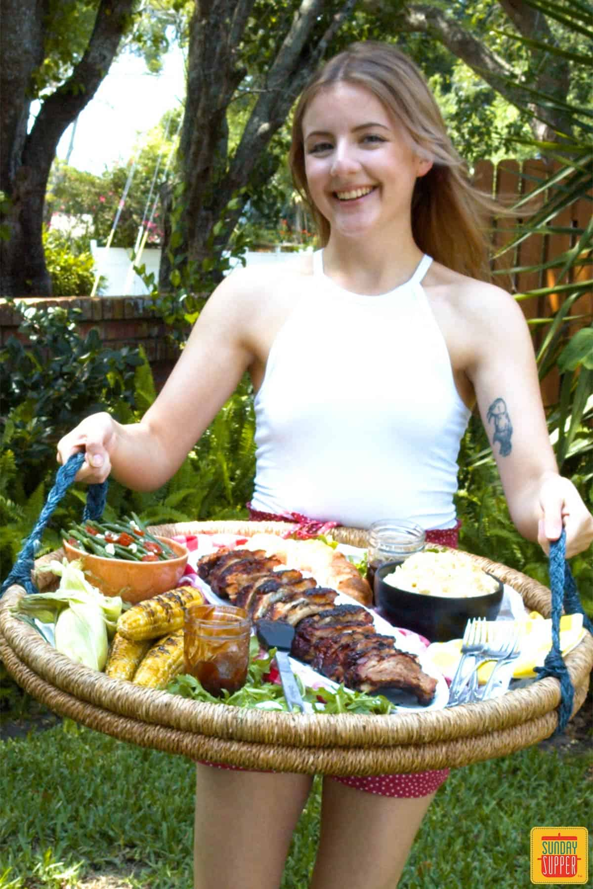 Smiling woman holding tray of baby back ribs and side dishes outside