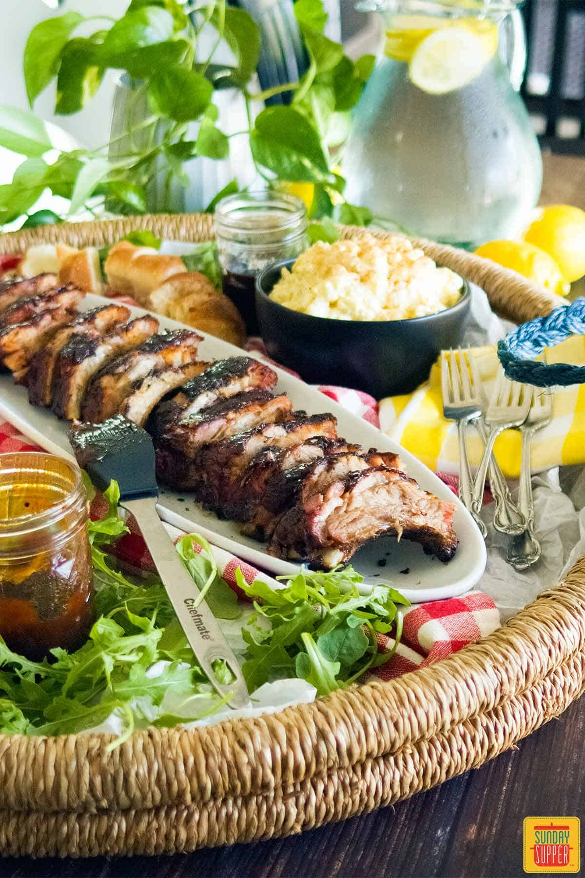 Sliced pork back ribs on a platter with side dishes