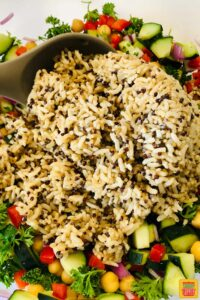 Mixing brown rice into quinoa salad