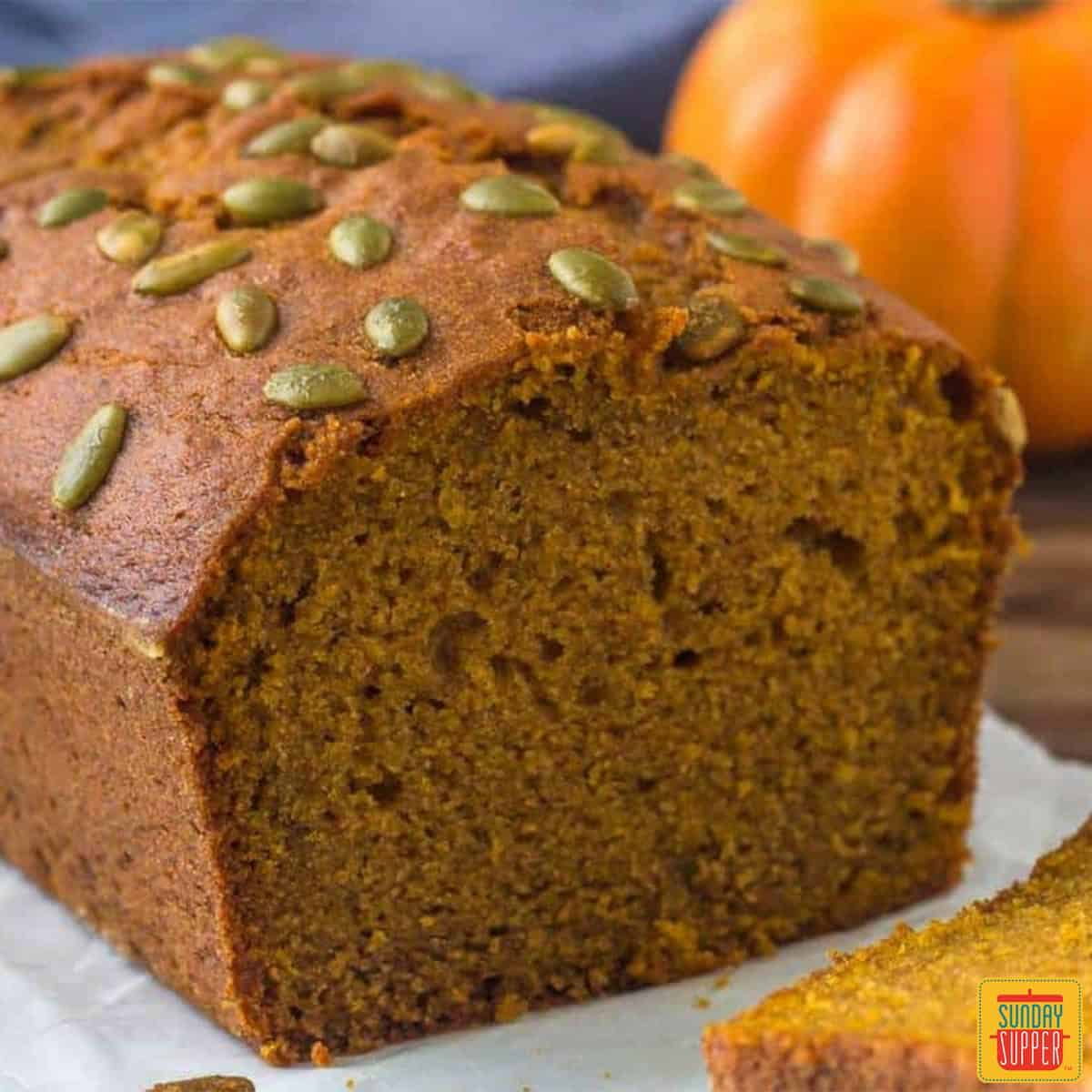 A loaf of Starbucks Pumpkin bread on a white platter with pumpkin seeds on top