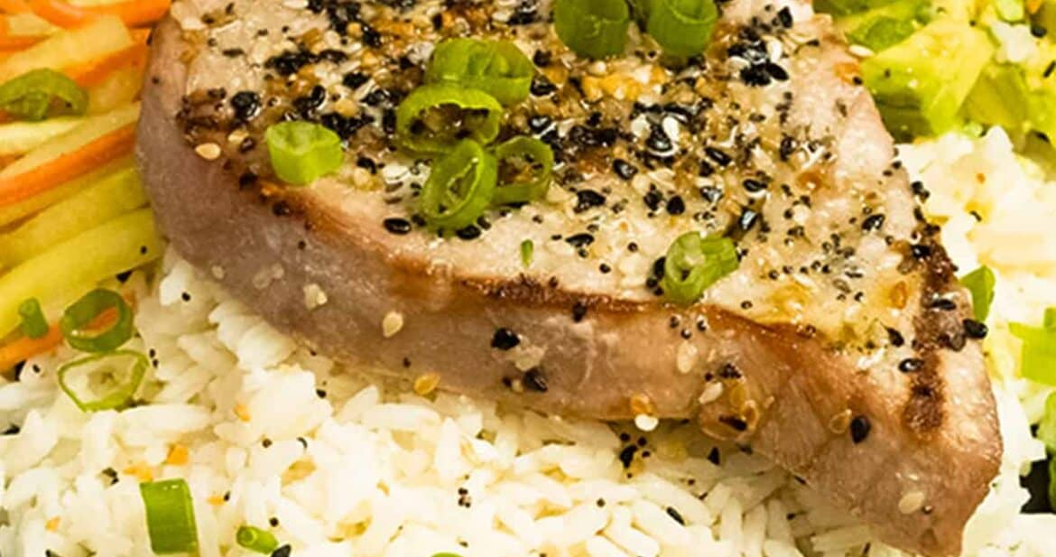 Grilled tuna steak on a bed of rice with vegetables and spicy mayo