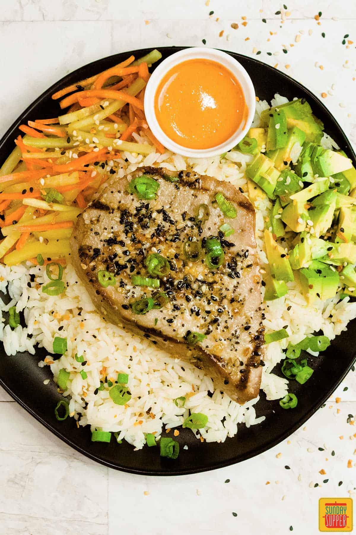 Tuna steak on a black plate seasoned with veggies