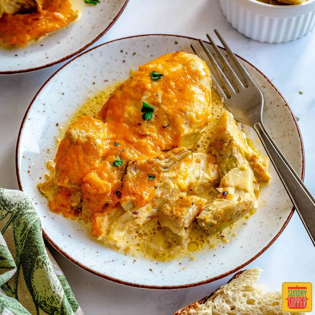 Chicken artichoke casserole on a plate with a fork