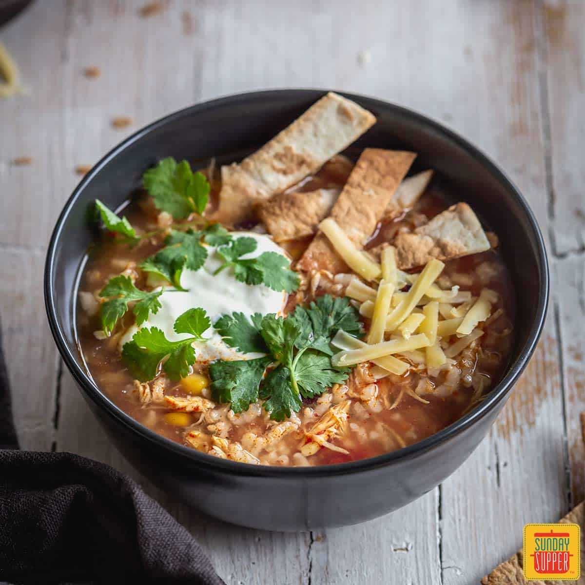 instant pot chicken and rice soup in a bowl with tortilla strips