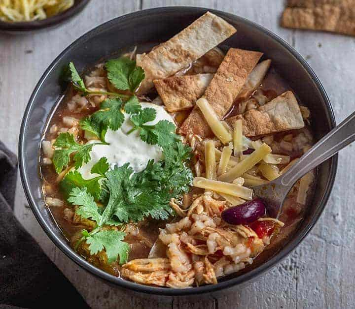 Completed bowl of Mexican Instant Pot chicken rice soup with tortilla strips