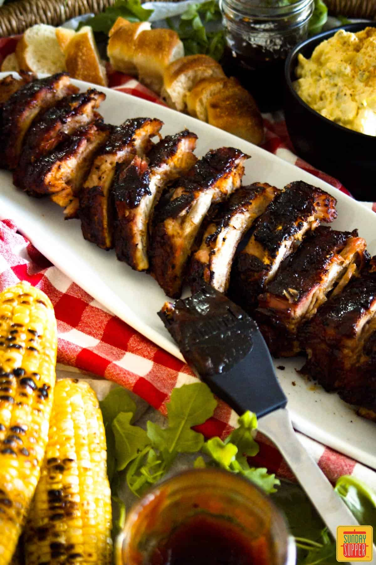 Baby Back Ribs on a white platter with corn