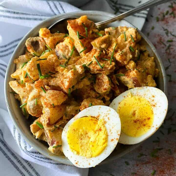 Spanish potato salad with two hard-boiled egg halves on a bowl