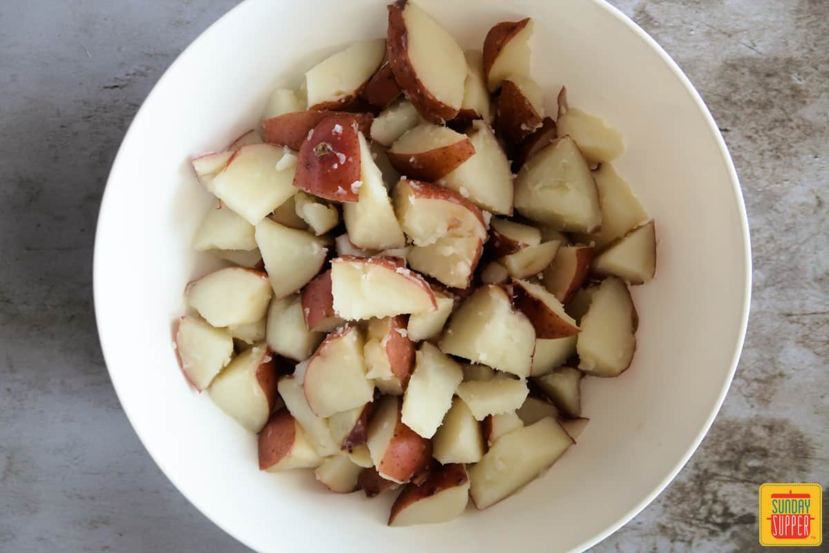 Chopped red potatoes in a white bowl