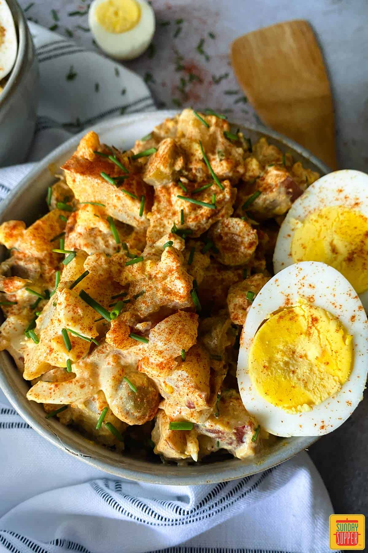 Close up of spanish potato salad in a bowl with hard boiled eggs