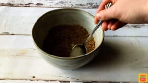 mixing potato seasoning in a bowl with a spoon