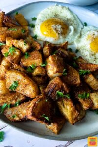 air fryer breakfast potatoes on a plate with two eggs