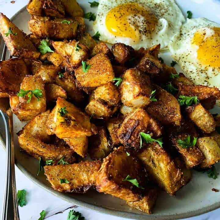 Air fryer breakfast potatoes up close on a plate with eggs