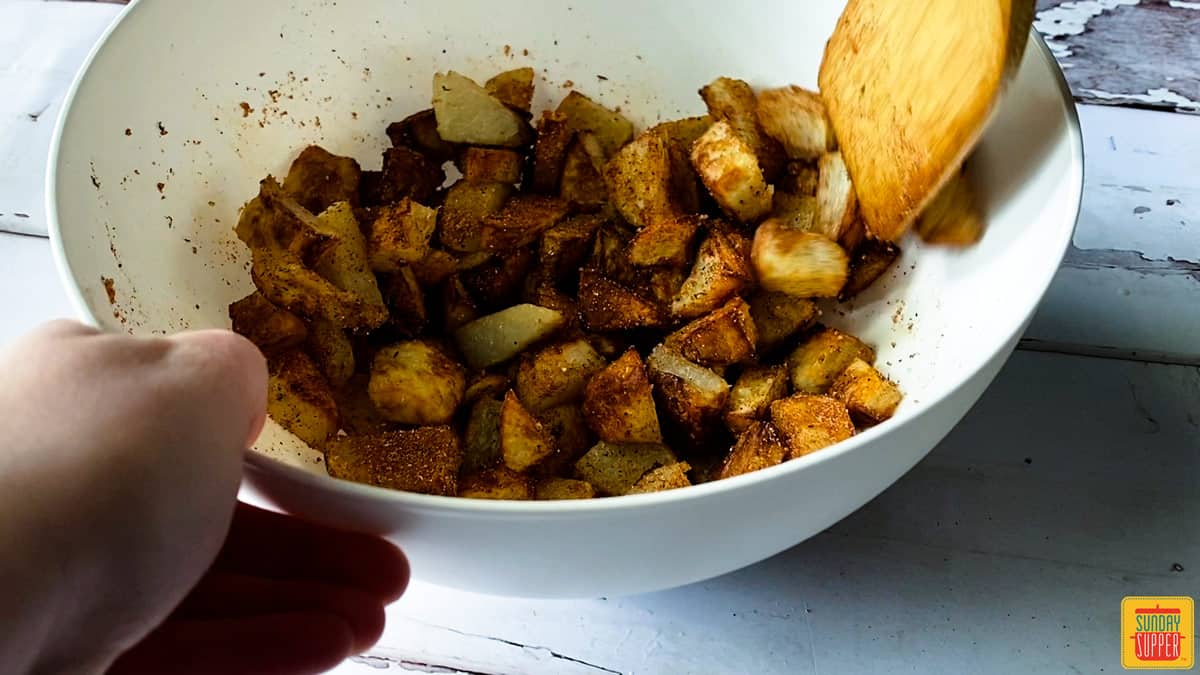 Mixing potatoes with seasoning in a bowl