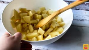 Mixing diced potatoes with oil