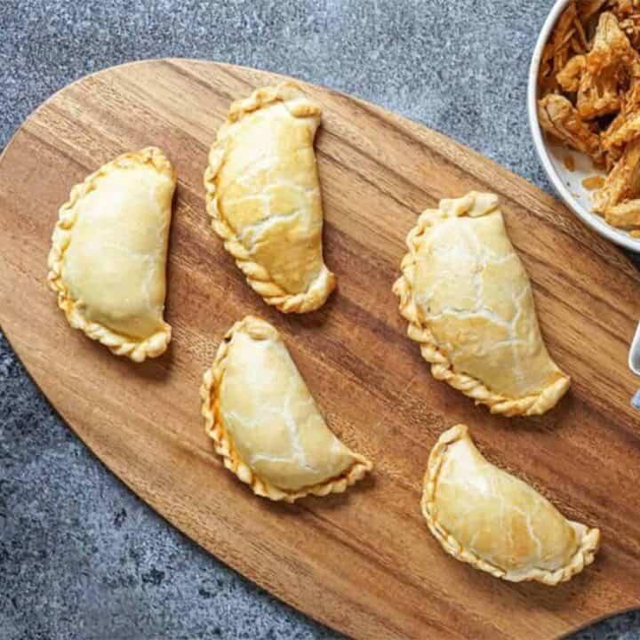 five empanadas on a cutting board