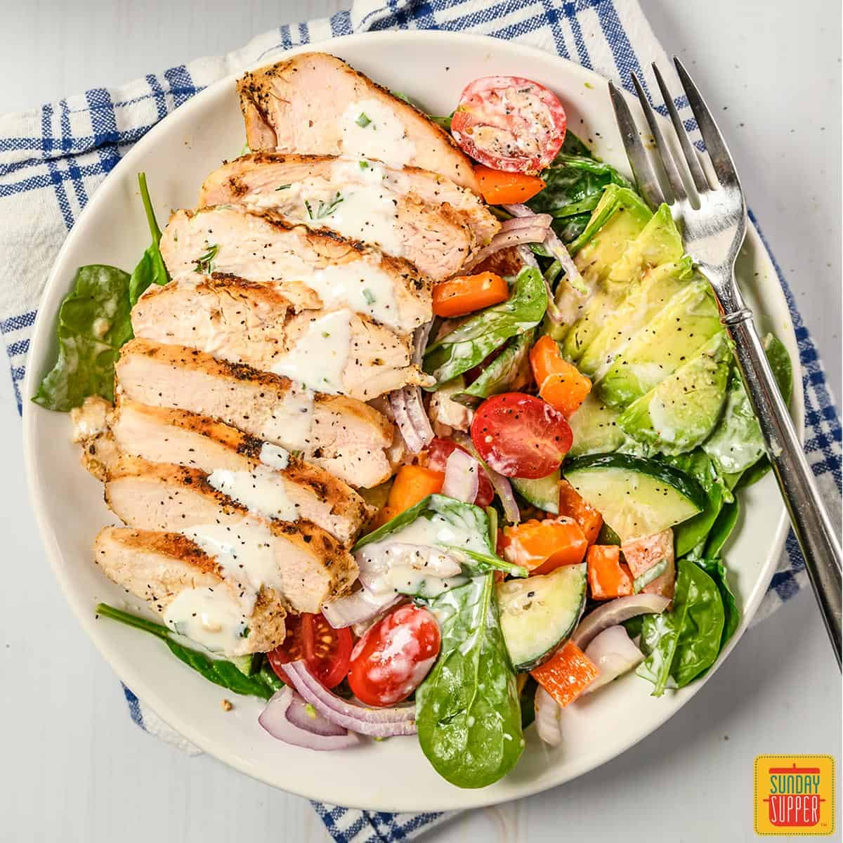 Slices of grilled chicken on a salad with buttermilk ranch dressing and a fork