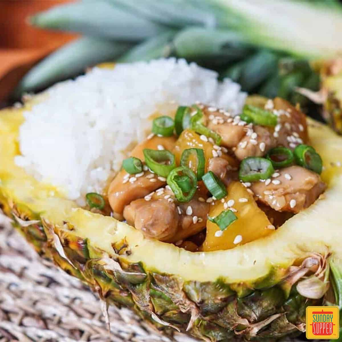 teriyaki chicken in a pineapple bowl with rice