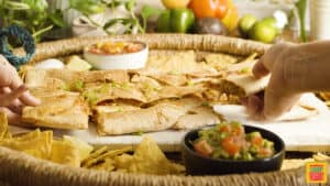 baked quesadillas on a serving platter with guacamole and chips