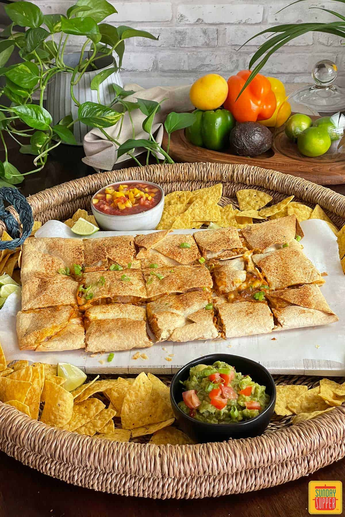 Baked quesadillas on a platter with guacamole, chips, and salsa