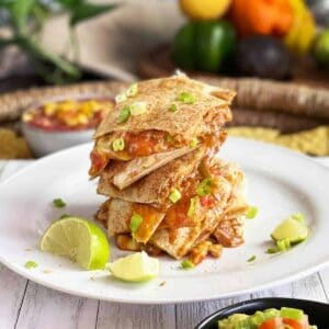 baked quesadillas stacked on a white plate