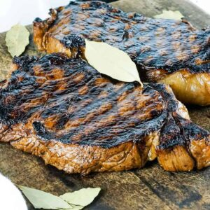 Grilled steaks with diamond marks on a cutting board