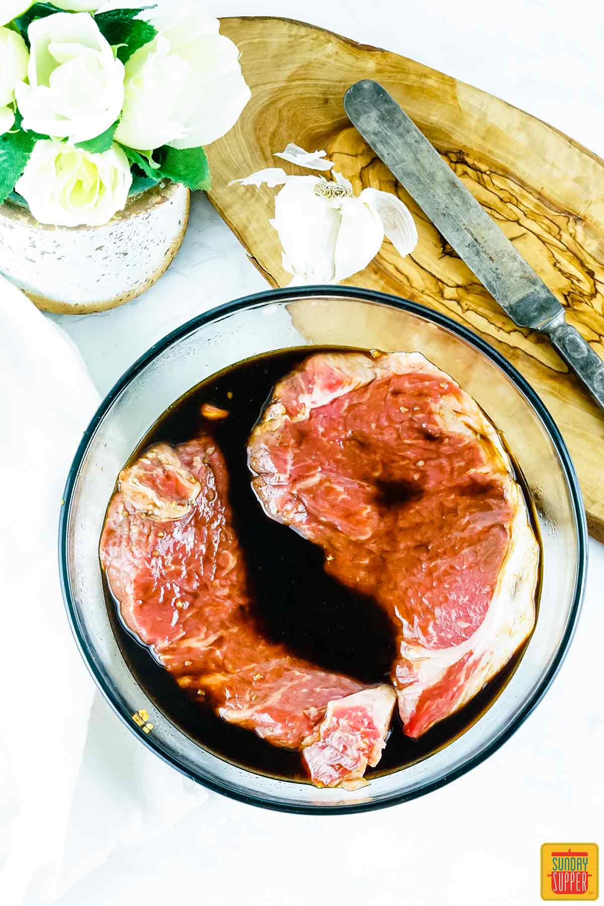 Two steaks marinating in a bowl
