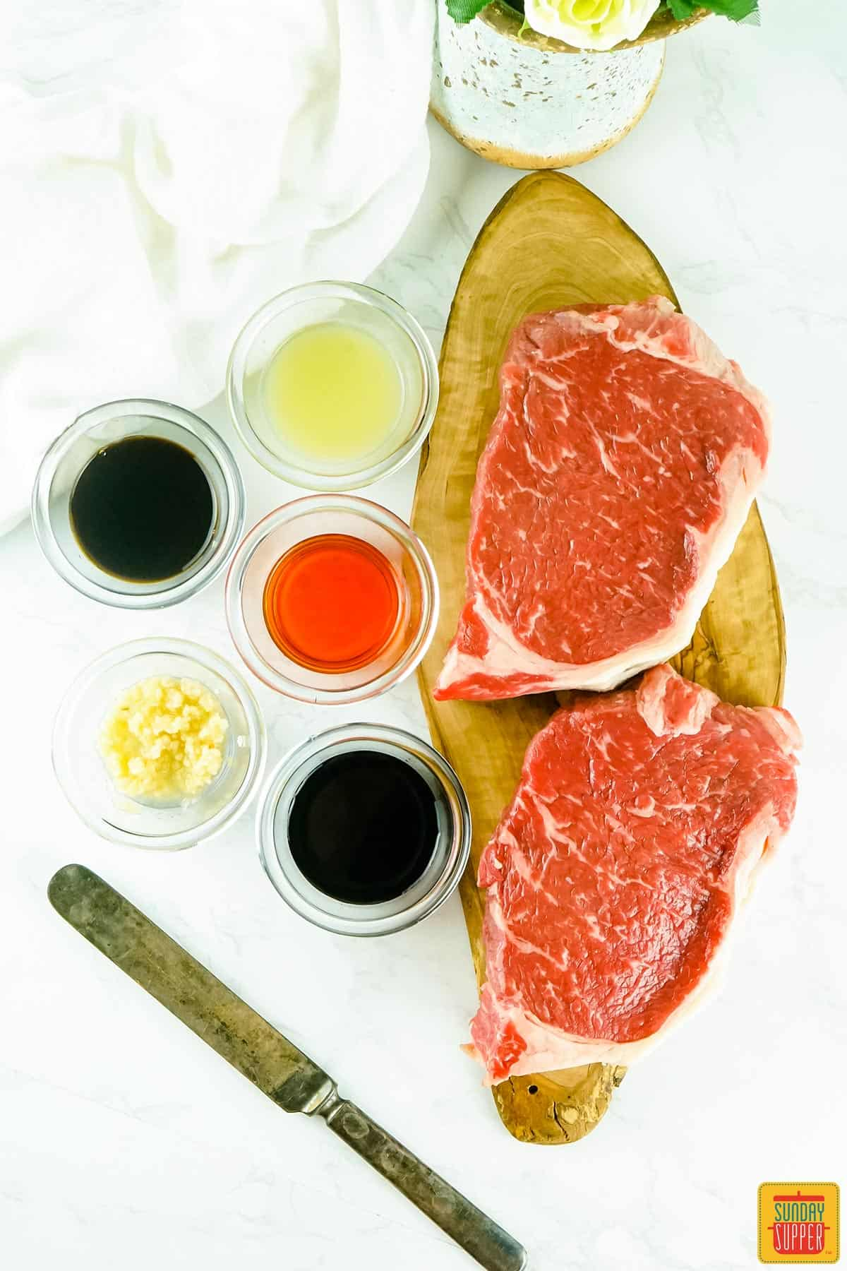Steaks on a cutting board next to marinade ingredients