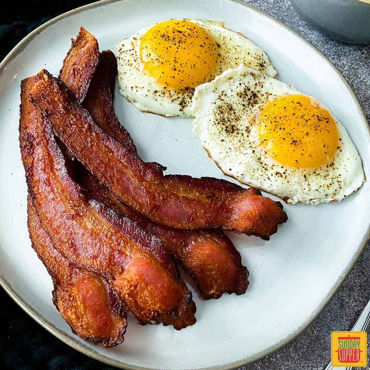 Air fryer bacon on a white plate with two sunny side up eggs
