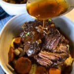 pouring gravy over slow cooker short ribs