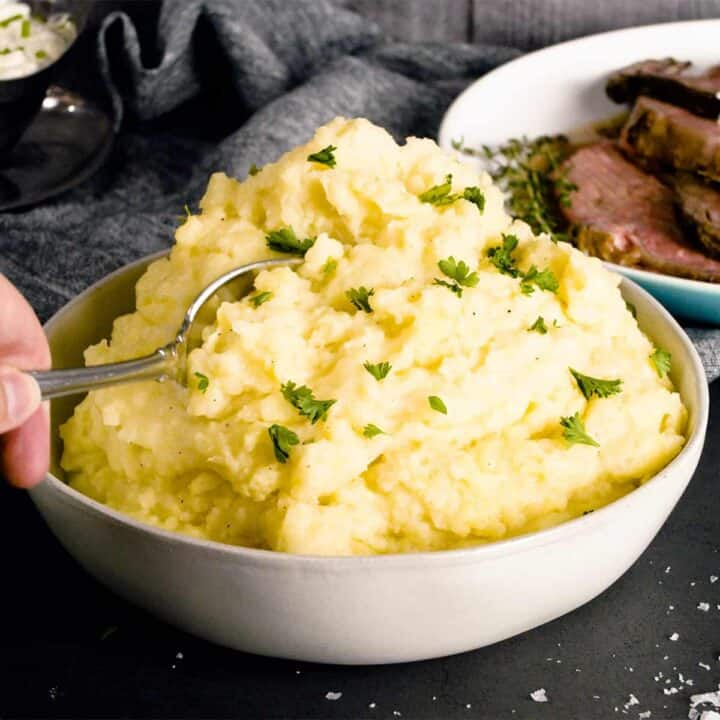 creamy mashed potatoes piled high in a white dish with a spoon and chives